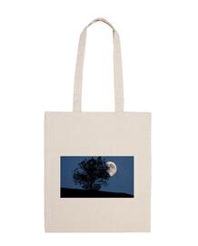 La Luna escondida entre los árboles