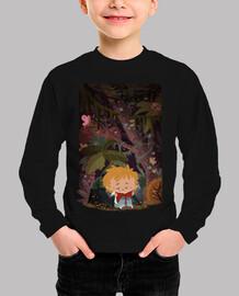 Niño leyendo en una selva